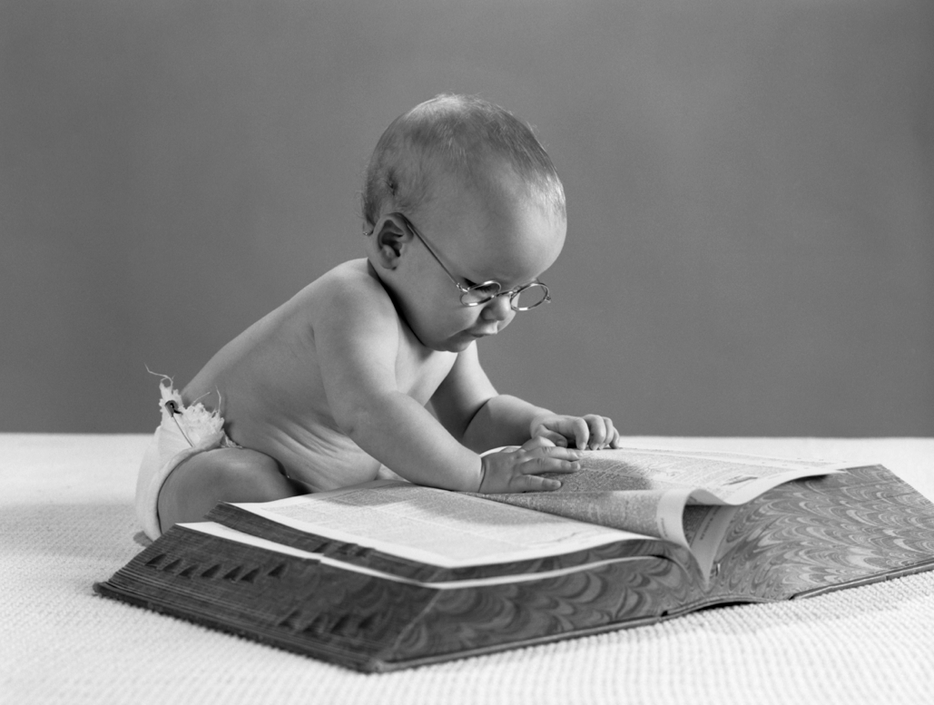 A baby reading a paper book