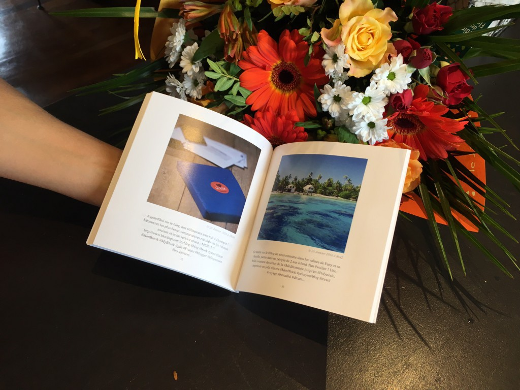 A paper book opened in front of flowers