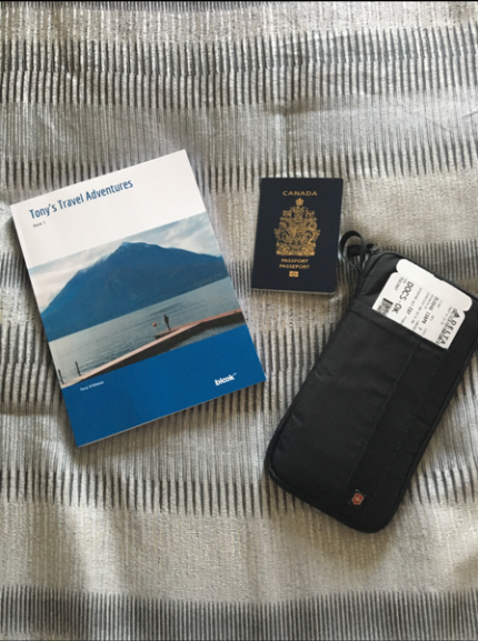 a blook a passport and a boarding pass on a bed