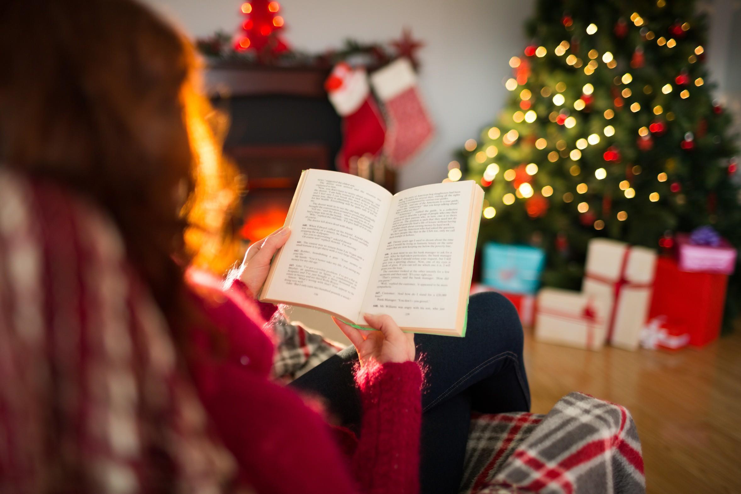 Rear view of redhead reading at christmas