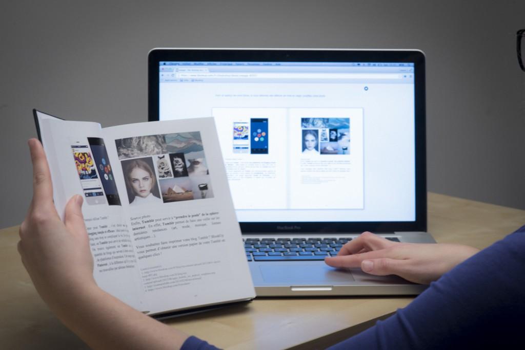 Une personne tenant le livre de son blog en face d'un écran