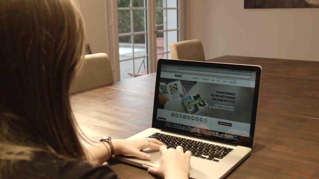 Une femme consultant le site internet de BlookUp pour créer un livre
