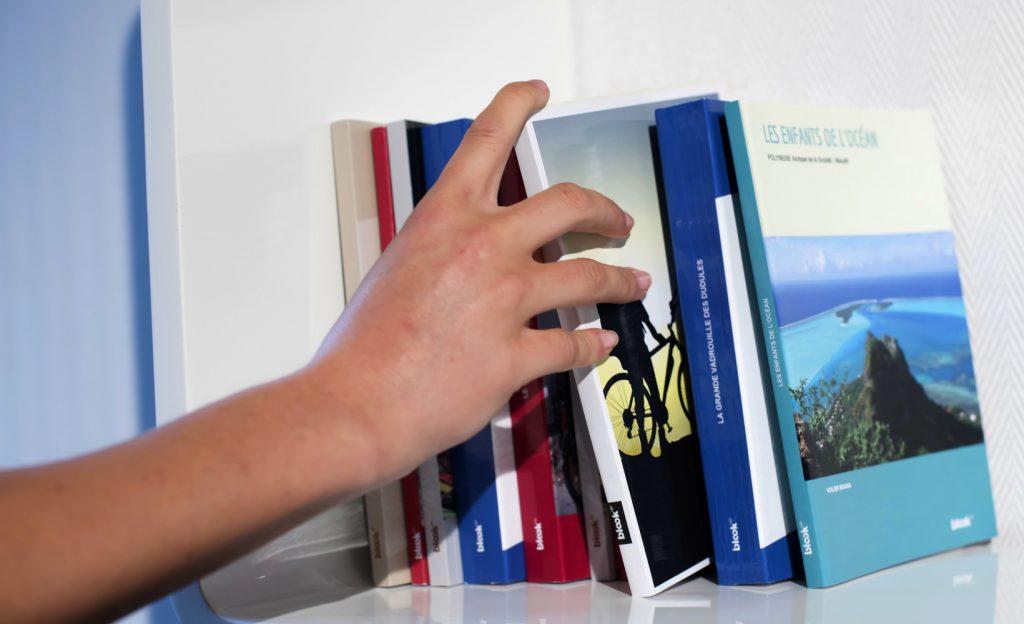 Livres sur une étagère, une main en choisit un