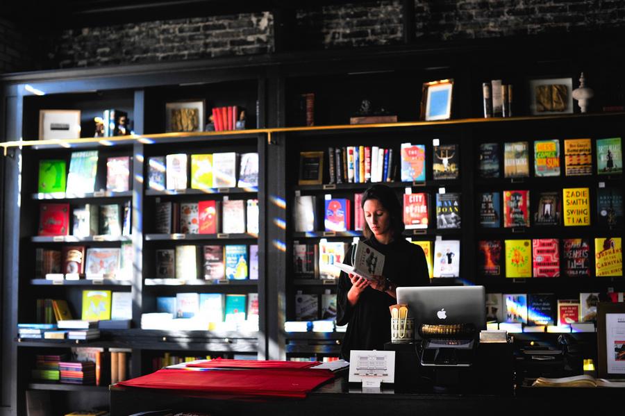 une personne dans une librairie lisant un livre