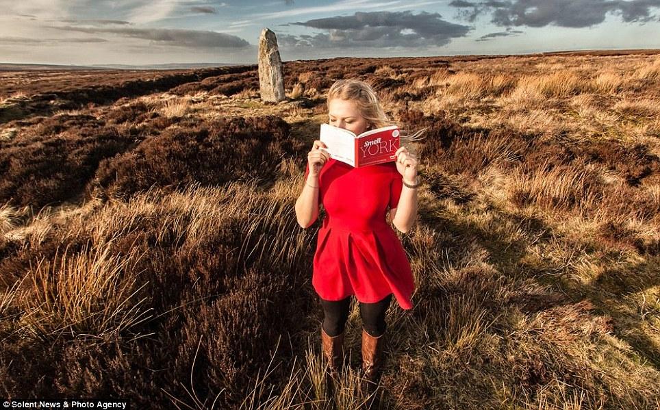 une femme grattant le livre guide olfactif à l'éxterieur