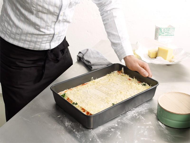 personne entrain d'utiliser le livre de recette de lasagne