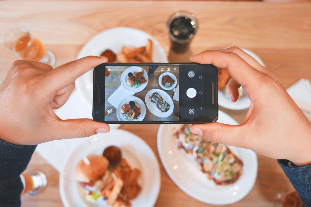 personne prenant une photo de nourriture sur sa story instagram