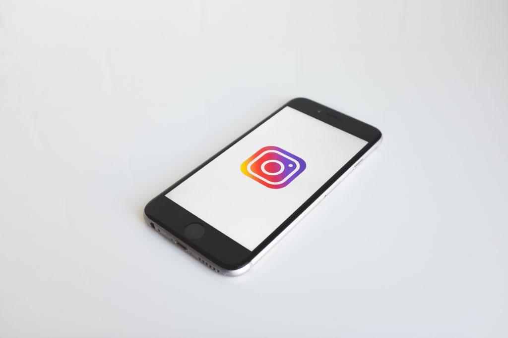 un iphone avec l'icone d'instagram sur un fond blanc